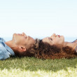 Young couple relaxing in grass - Stock Photo