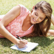 Royalty-Free Stock Photo: Happy woman writing in park
