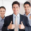 Business team showing you thumbs up - Stock Photo