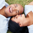 Smiling young couple lying together on grass - Stockfoto