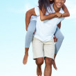 Young female enjoying piggyback ride on her boyfriend - Stockfoto