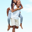 Smiling young couple playing piggyback - Stockfoto