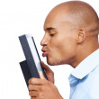 Happy afroamerican businessman kissing a computer screen on whit - Zdjęcie stockowe