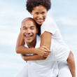 Joyful young man carrying girlfriend on his back - Stockfoto