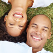 Afroamerican young couple in love lying on grass - Stockfoto