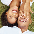 Romantic young couple having fun while lying on grass - Stockfoto