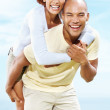 Happy young couple enjoying a piggy back ride - Stock Photo