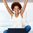 Excited woman sitting with laptop - Photo