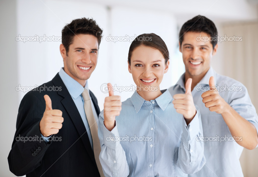 Portrait of beautiful business woman with male colleagues giving you thumbs up — Stock Photo #7875737