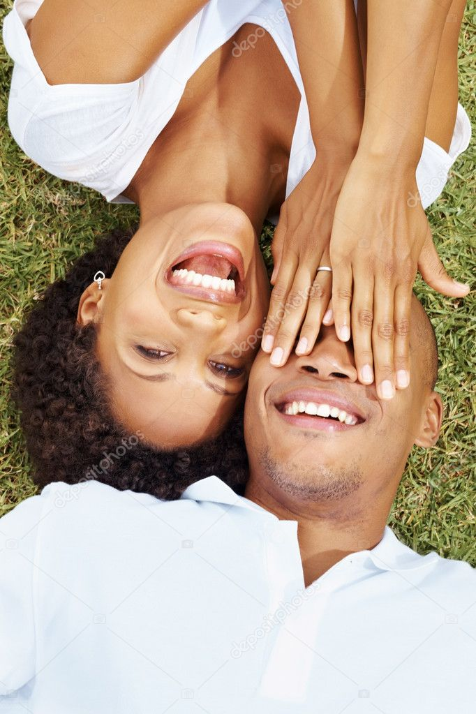 Pretty young woman covering his boyfriend's eyes as they both lying on grass together — Stock Photo #7878021