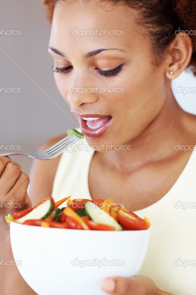 Closeup of beautiful African American woman eating vegetable salad  Stock Photo #7879274