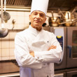 Smiling male chef in commercial kitchen - Stock Photo