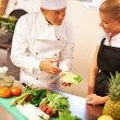 Chef giving culinary lessons to trainee - Stock Photo