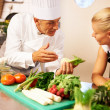 Chef explaining trainee about chopping vegetable - Stock Photo