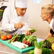 Chef giving cooking lessons to trainee - Stock Photo