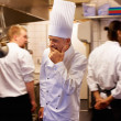 Tired chef with colleagues in kitchen - Stock Photo