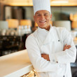 Smiling cook with arms crossed - Stock Photo