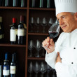 Male chef tasting red wine - Stock Photo