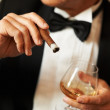 Man in tuxedo holding cigar and glass of brandy - Stock Photo