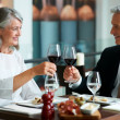 Mature couple celebrating at restaurant - Zdjęcie stockowe