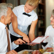 Smiling waitress helping senior couple a dish choice - Zdjęcie stockowe