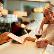 Female barmaid taking order from senior couple - Stock Photo