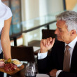 Mature man having meal at restaurant with his wife - Stock Photo