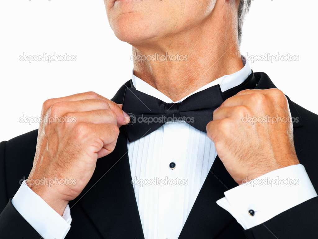 Closeup of business man adjusting neck bow over white background  Stock Photo #7880480