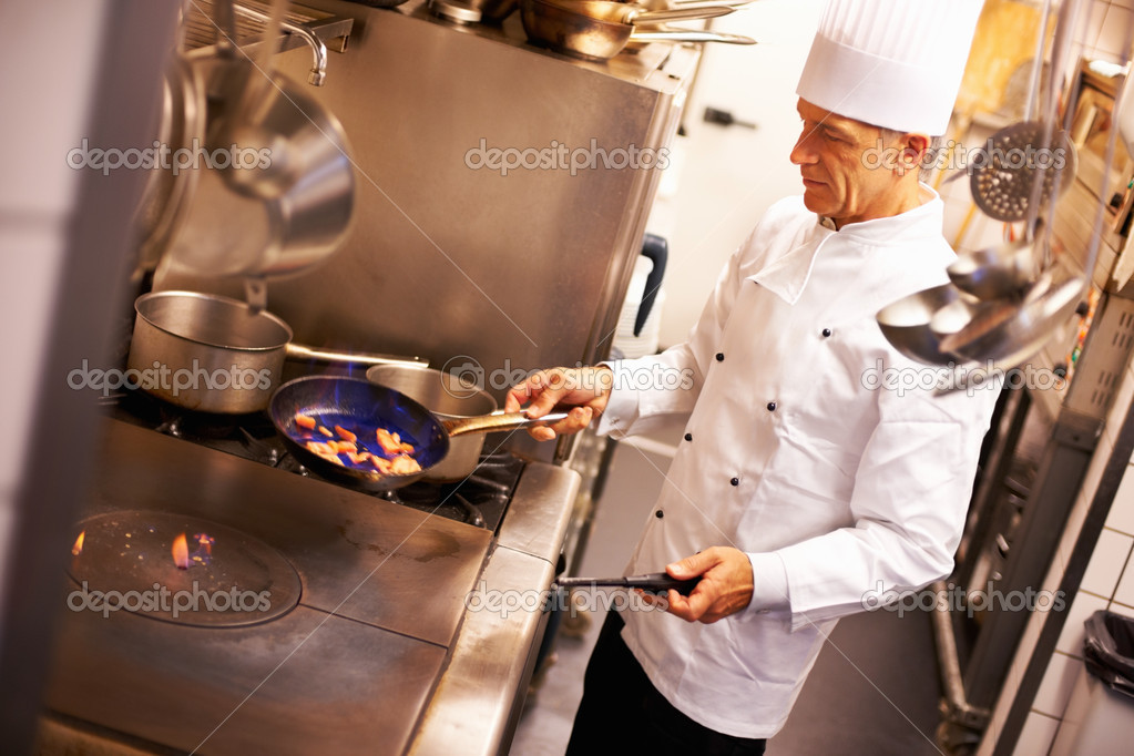 Portrait of handsome chef cooking food in kitchen — Stock Photo #7880878
