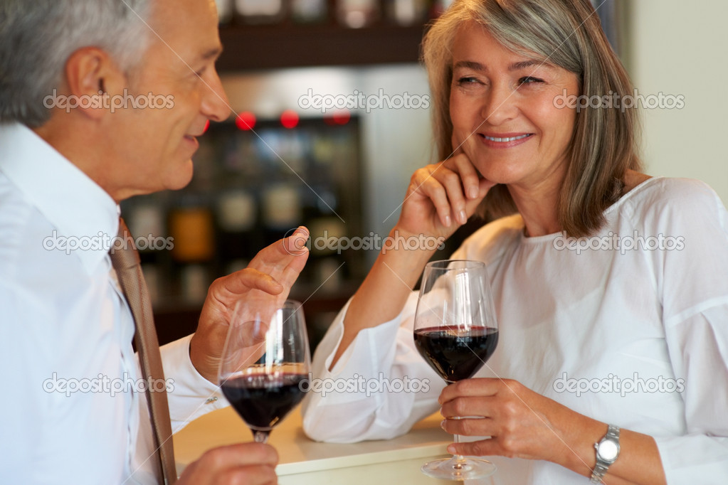 Mature couple enjoying a drink at bar together smiling  Stock Photo #7881120