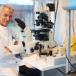 Royalty-Free Stock Photo: Happy mature male researcher with microscope