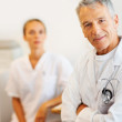 Royalty-Free Stock Photo: Confident male doctor with a nurse at the back