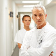 Senior caring doctor with a nurse at the back - Foto Stock