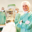 Successful male surgeon in operation theater with team at back - Stock Photo