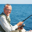 Royalty-Free Stock Photo: Smiling senior man in glasses fishing on the beach on sunny day