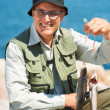Portrait of handsome mature man in glasses holding his catch on the beach - Stok fotoğraf