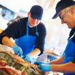 Fishmongers arranging fresh seafood - Stock Photo