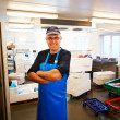 Happy fishmonger in his workplace - Stock Photo