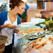 Woman looking at a fresh fish display - Foto de Stock  