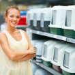 Smiling woman at pet shop - Stock Photo