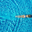 Top view of young woman swimming underwater in the pool - Stock Photo