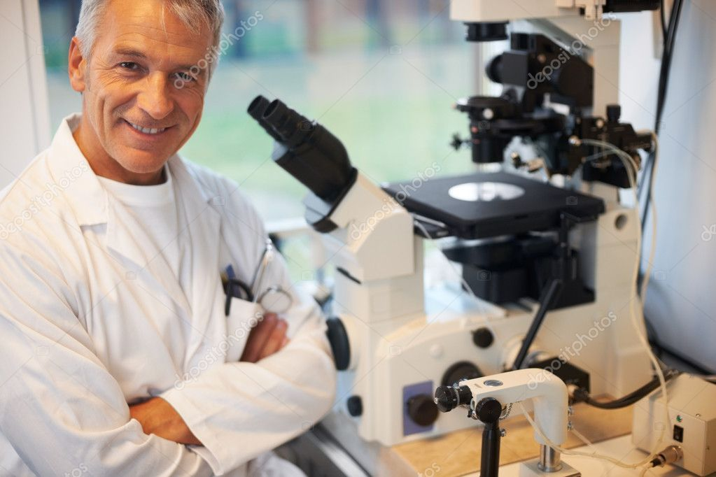Portrait of smiling mature male scientist in laboratory with a microscope — Stock Photo #7892935