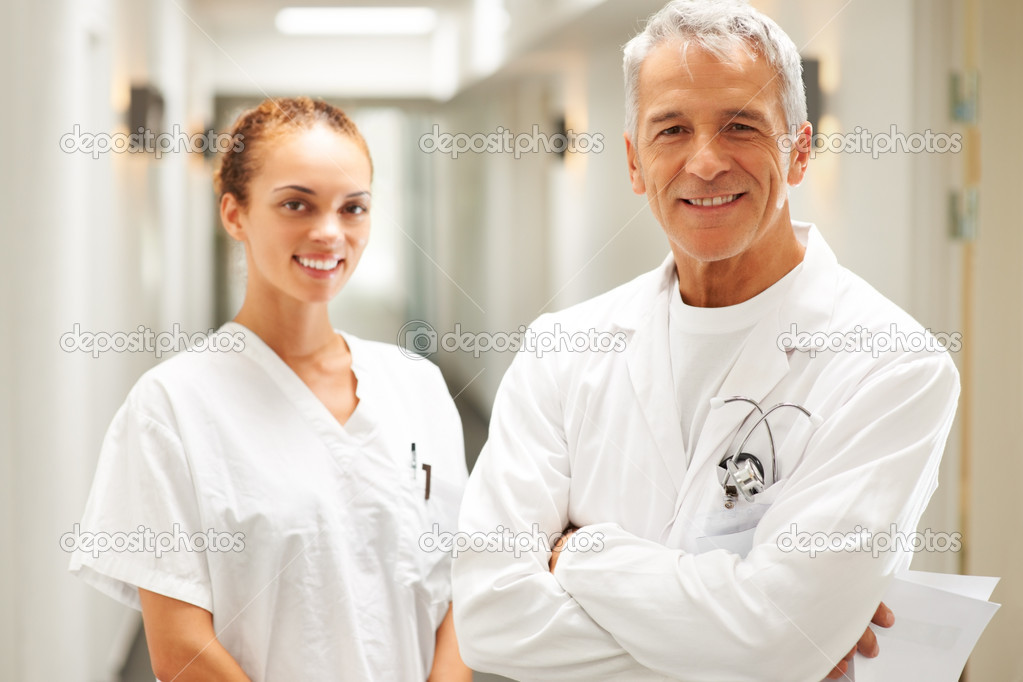 Portait of male and female doctor standing together and smiling at hospital — Stok fotoğraf #7893261
