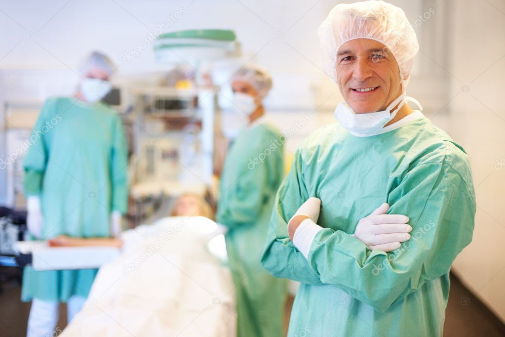 Portrait of confident male surgeon with assistants in background in operation theater — Stock Photo #7893494