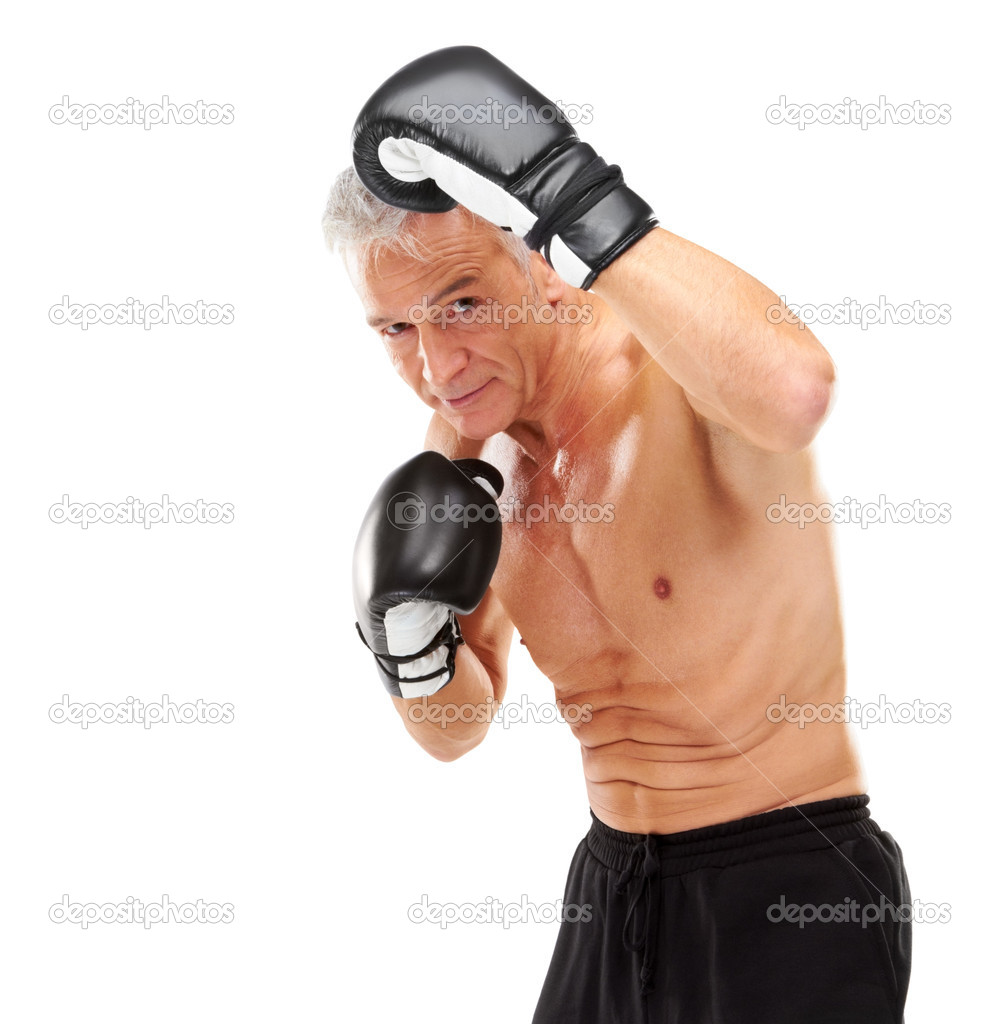 Portrait of mature man with boxing gloves exercising the moves against white ...