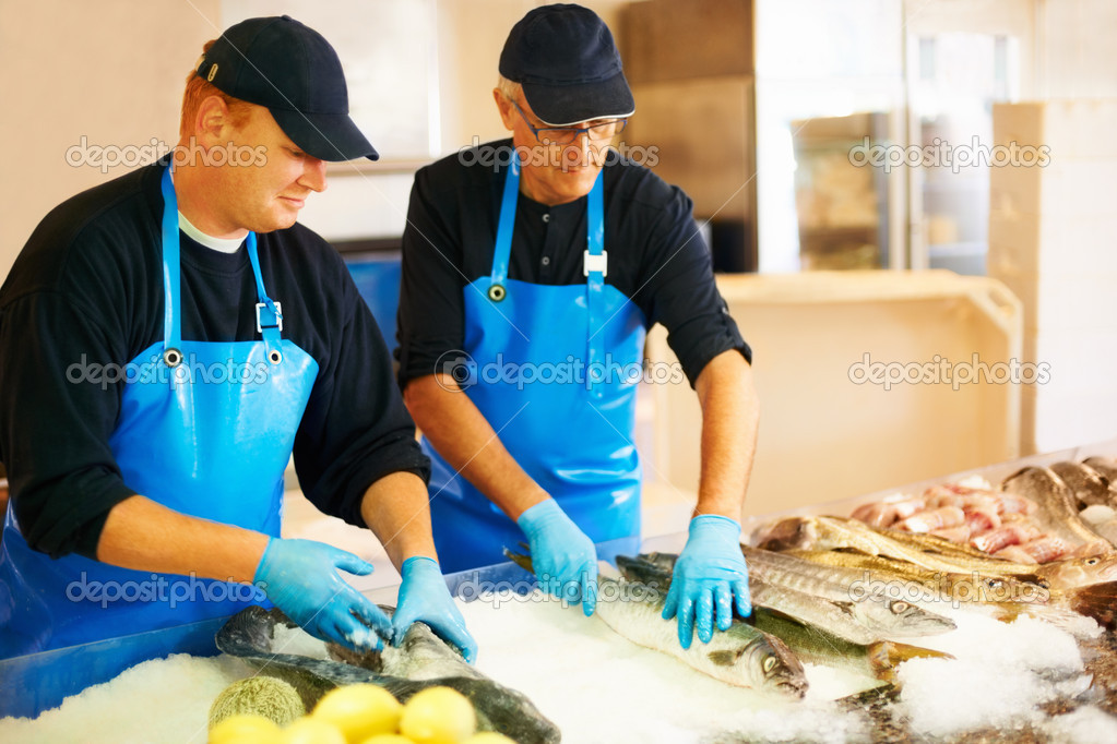 Two workers arranging fresh fish on ice — Stock Photo #7894246