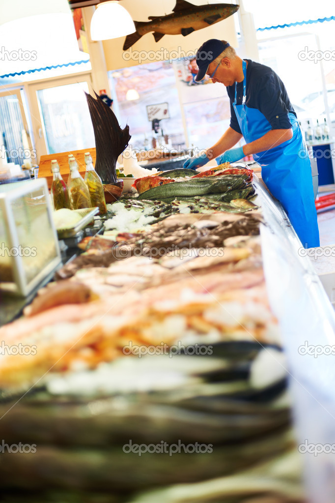 Mature worker unpacking fresh fish — Foto Stock #7894250