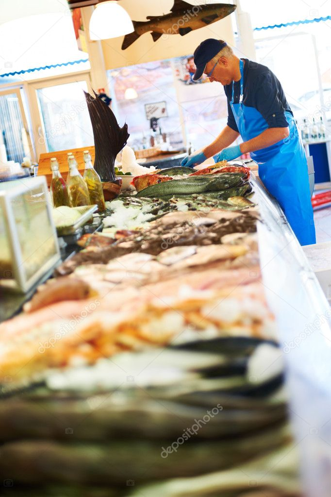 Mature worker unpacking fresh fish — ストック写真 #7894250