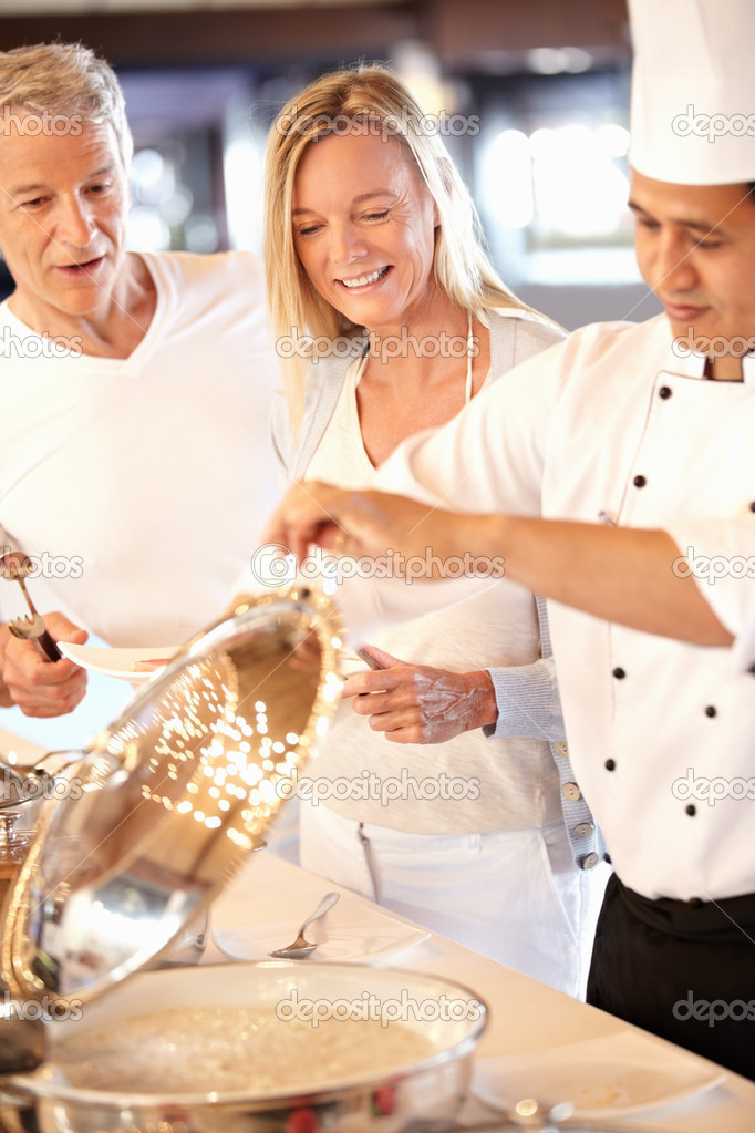 Happy chef serving food to beautiful mature couple — Stock Photo #7898629