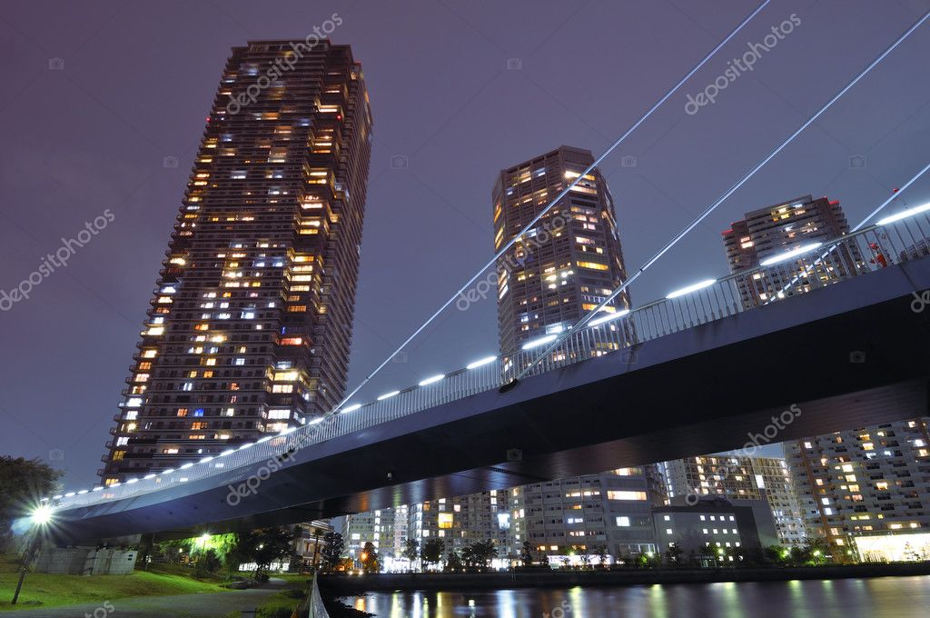 Huge residential skyscrapers with illuminated windows beyond illuminated suspension bridge structure in Tokyo, Japan — Stock Photo #7184969